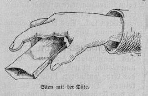 Das Bild zeigt eine Hand und ein Tütchen beim Samen aussäen